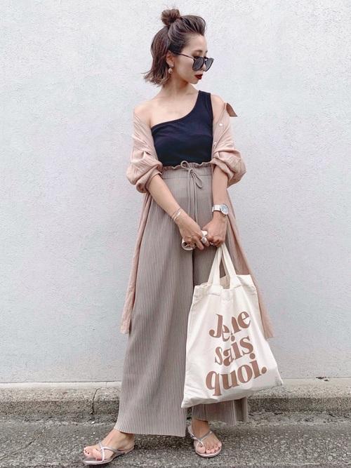 黒のワンショルタンクにベージュのリブパンツを合わせて、ベージュの薄手ロングシャツを羽織った女性