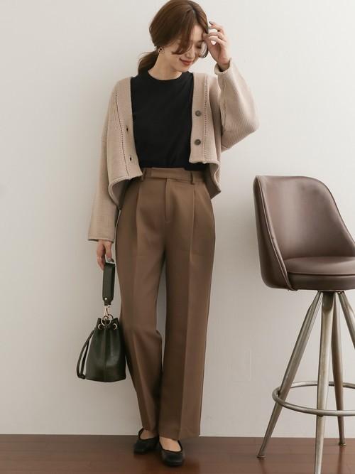 黒Tにブラウンのパンツを合わせて、ベージュのニットカーデを羽織った女性