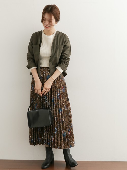 ベージュのカットソーにブラウンの花柄プリーツスカートを合わせて、カーキのブルゾンを羽織った女性