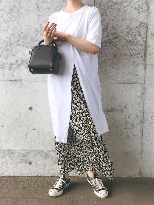 白のスリット入りTシャツワンピに黒の花柄スカートを合わせた女性