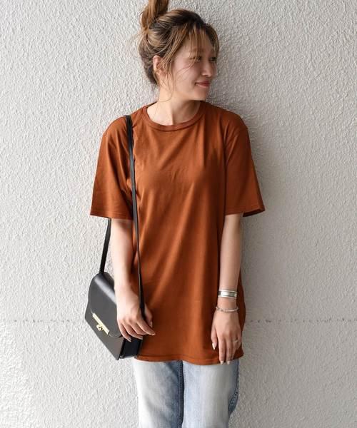 キャメルTシャツにデニムパンツコーデの女性