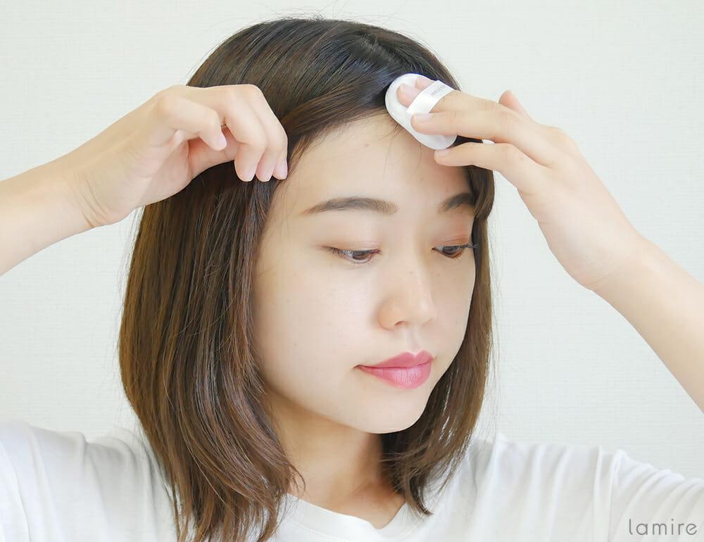 イニスフリーのノーセバムミネラルパウダーを前髪の根元に塗布している女性の写真