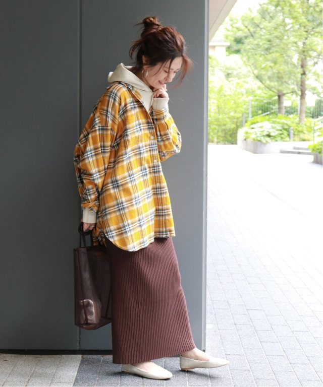 イエローのチェック柄シャツにフーディーをレイヤードして、ブラウンのリブスカートを合わせた女性