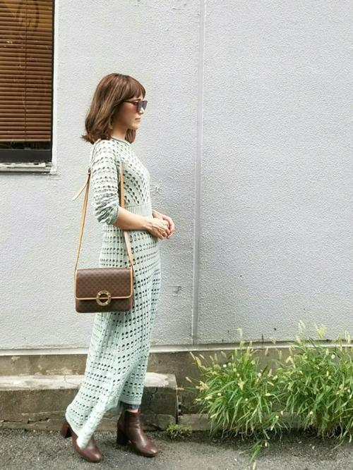 グリーンの柄ワンピースにブラウンのブーツを合わせた気温20度の日にぴったりなレディースの服装