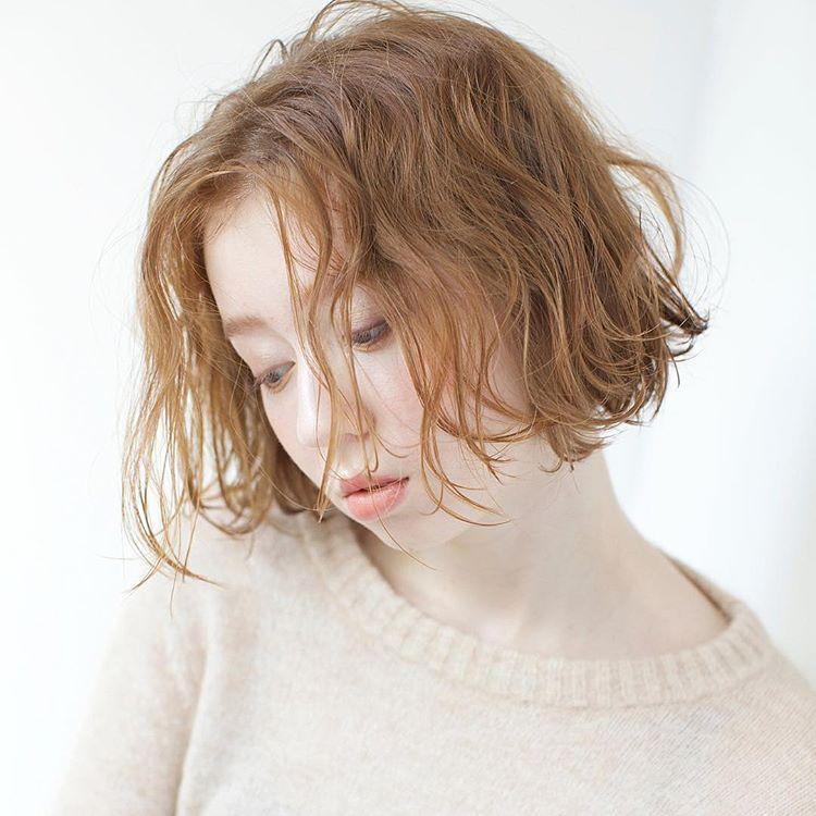ブリーチありの髪色にオレンジ系のヘアカラーをした前髪なしのパーマボブヘアスタイルの女性
