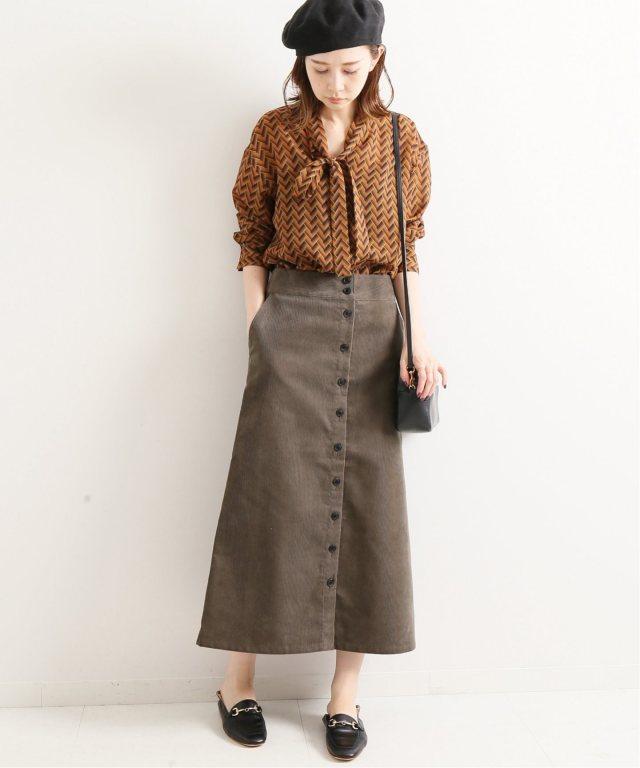 ベージュのボウタイブラウスにグレーのフロントボタンコーデュロイスカートを合わせた女性