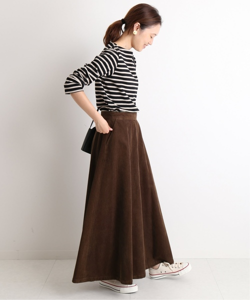 ボーダーTシャツにブラウンのコーデュロイスカートを合わせた女性