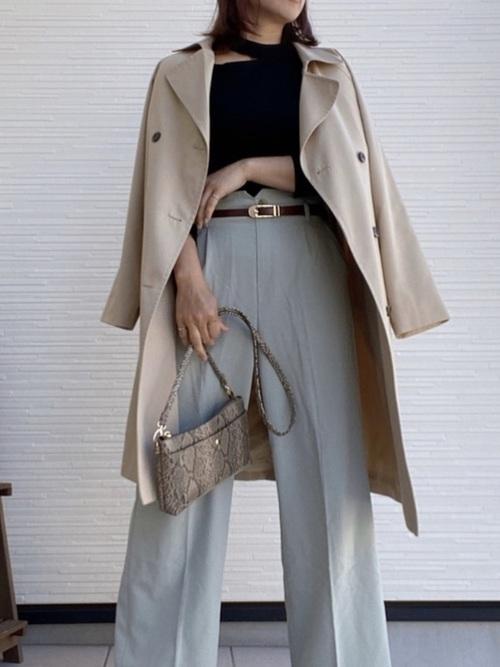 ブルーのパンツに黒のトップス、チェスターコートとパイソン柄のバッグ