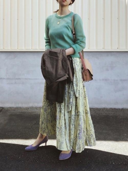 緑トップスと花柄スカートコーデの女性