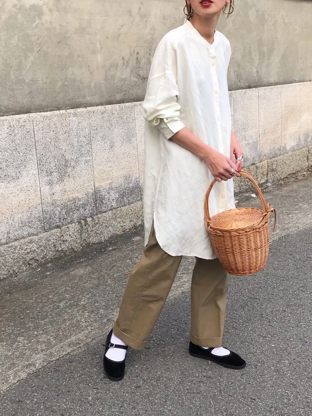 リネン素材の白ロングシャツとパンツスタイルのコーデの女性
