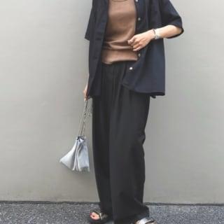 黒いパンツにシャツをきた女性