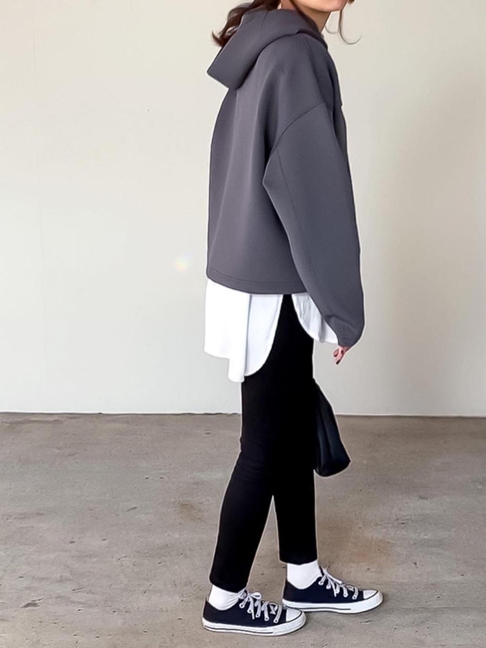 グレーパーカーに白シャツと黒スキニーを着用している女性の写真