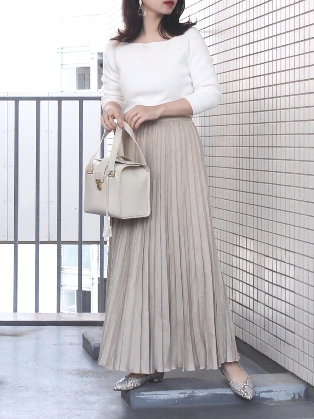 白カットソーにベージュ系のプリーツスカートとパイソンのサンダルを履いている女性の写真