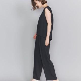 パンツスタイルの黒オールインワンを着ている女性の写真