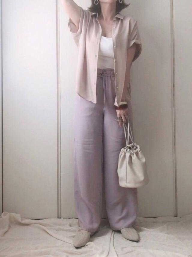 guのベージュエアリーシャツに紫のパンツ、白のバッグを持つ女性。