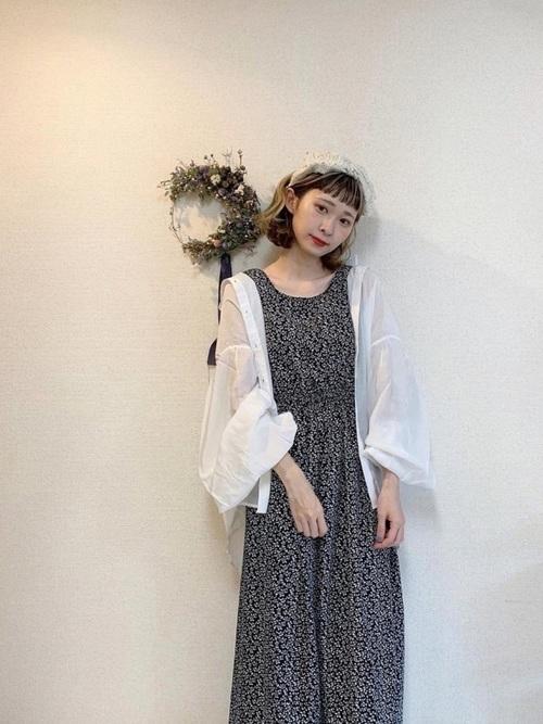 黒い小花柄のワンピースに白いシアーなシャツを合わせたコーデ