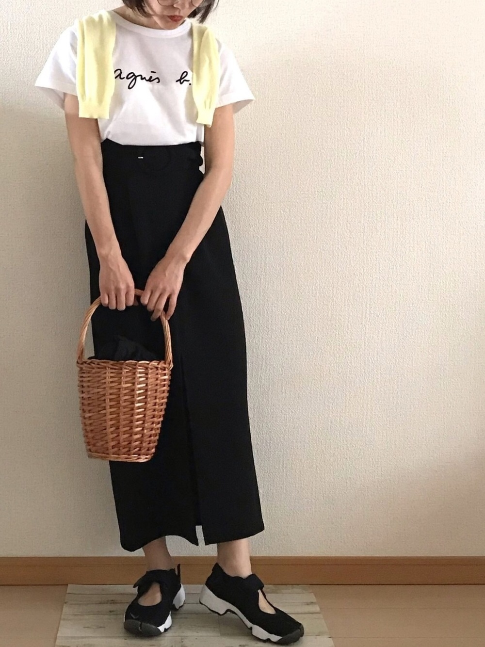Tシャツとタイトスカートのモノクロコーデに淡い黄色のカーディガンを羽織る女性