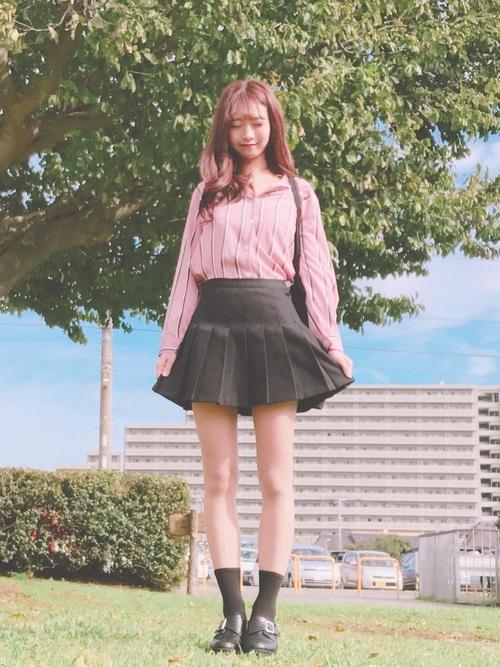 ピンクのストライプシャツと黒のテニススカートを合わせたコーディネート