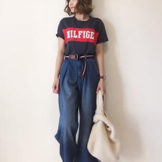 Tシャツにブルー系のワイドデニムパンツと白のスニーカーを履いた女性