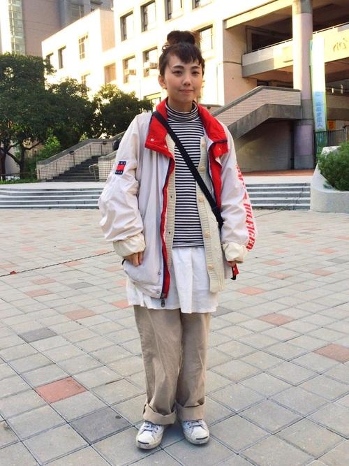 ホワイト系のナイロンジャケットにベージュのパンツとスニーカーを履いた女性