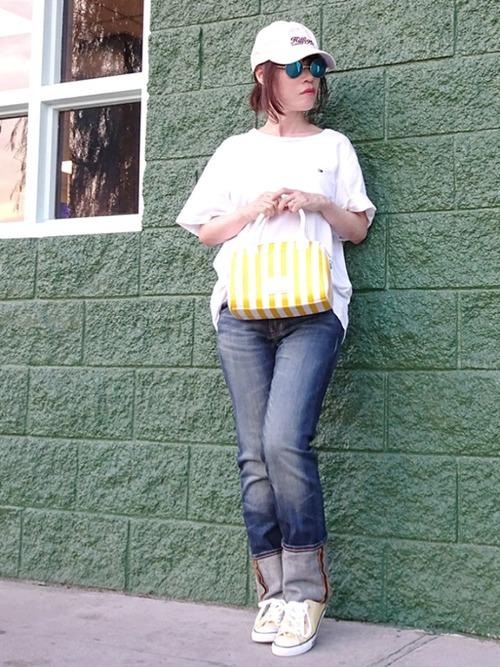 白のキャップとTシャツにブルー系のデニムパンツを履いた女性