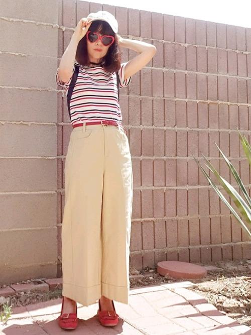 白のキャップとTシャツにベージュのワイドパンツを履いた女性