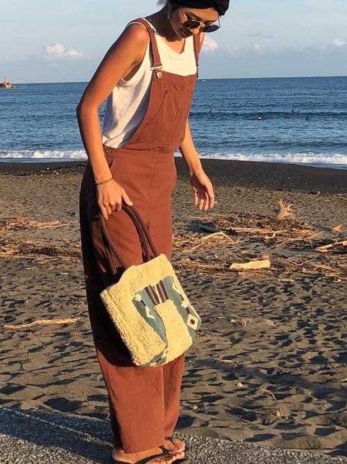 白のタンクトップにブラウン系のワイドサロペットを着て黒のクロックスビーチサンダルを履いた女性