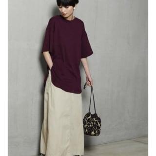 ボルドーTシャツにロングスカートを着た女性