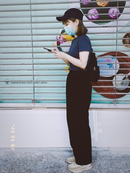 ネイビーのTシャツに黒のワイドパンツの女性
