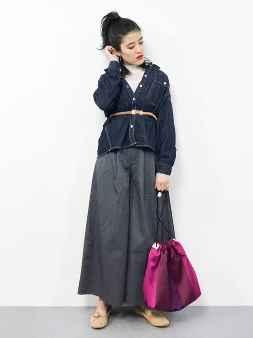ボリュームデニムシャツとダークグレーワイドパンツにベージュフラットシューズを履いた女性