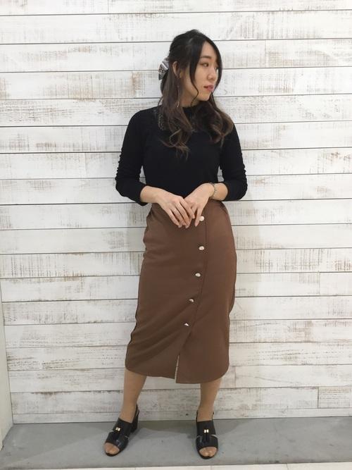 黒カットソーとむらのタイトスカートを着た女性