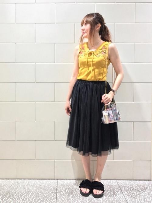 しまむらのイエロータンクトップと黒チュールスカートを着た女性