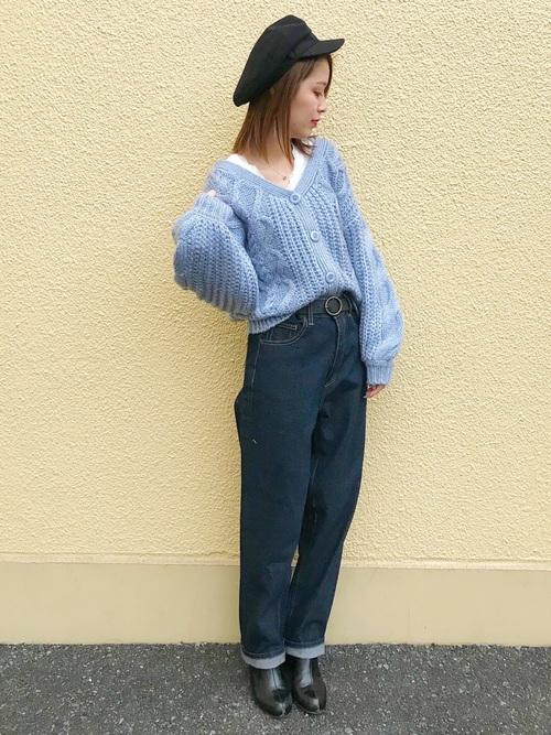 黒キャスケットとブルーケーブル編みショートカーディガンにロールアップジーパンを履いた女性