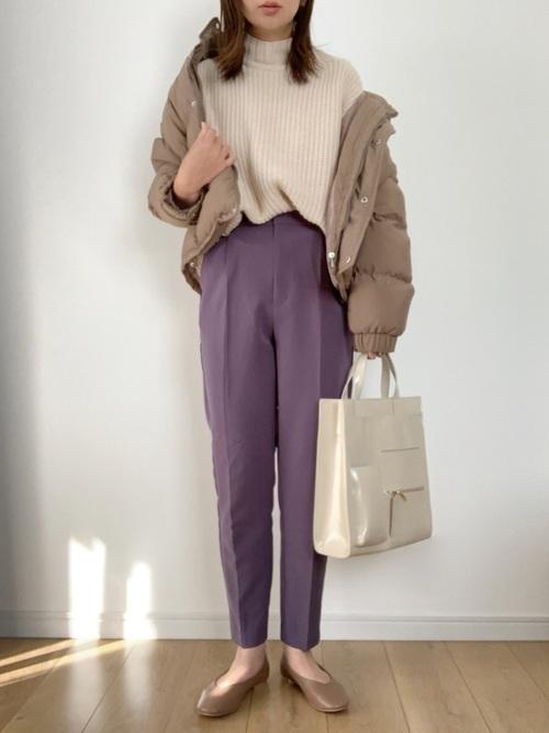 ダウンジャケットにテーパードパンツを履いた女性
