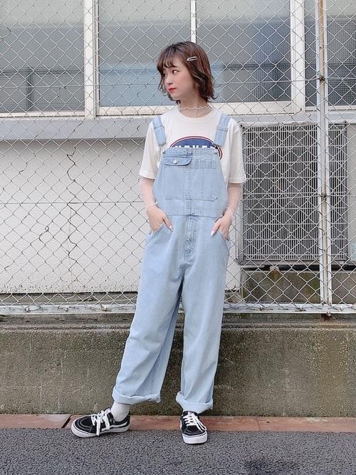 白プリントTシャツにオーバーオールを着た女性