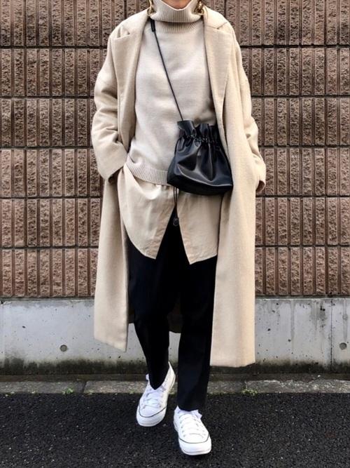 ビッグチェスターウールコートとタートルネックウールニットプルオーバーに黒テーパードシルエットズボンを履いた女性