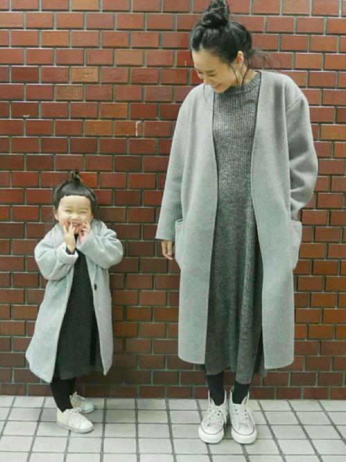 グレー着流しノーカラーコートとチャコールグレーリブニットワンピースに白スニーカーを履いた女性