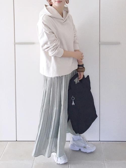 白ワイドシルエットパーカーとグレーサテンプリーツスカートに白スニーカーを履いた女性