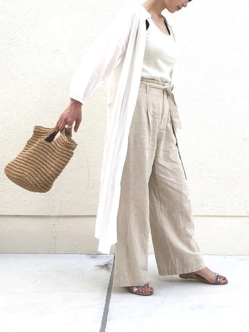 白フロントボタンリネンワンピースとベージュベルテッドリネンワイドパンツにアンクルストラップサンダルを履いた女性