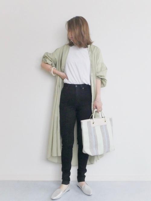 カーキシャツワンピースと白クルーネックTシャツにブラックスキニーデニムパンツを履いた女性