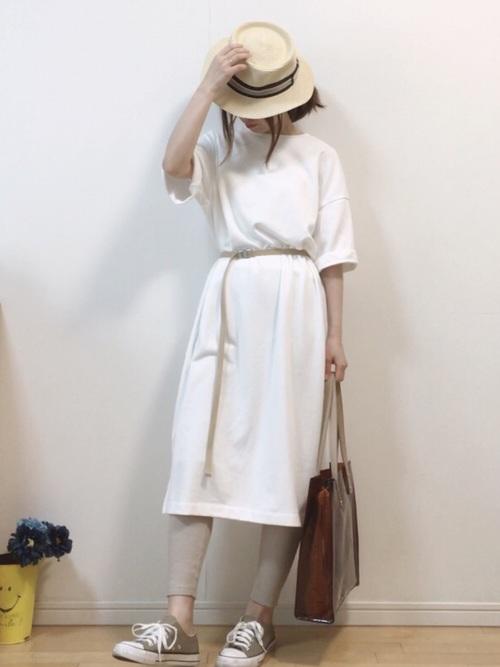 白スウェットスリットワンピースとカーキレギンスにカンカン帽を履いた女性