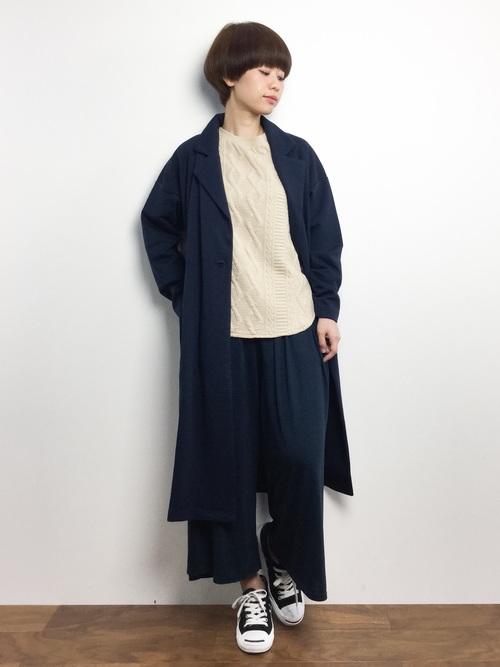 紺フロントタックガウチョパンツとベージュケーブルジャガープルオーバートに紺カットテーラーコートを履いた女性