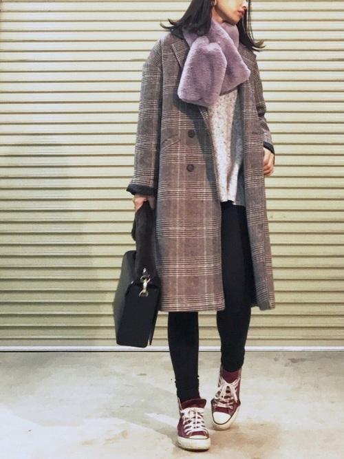 ダブルボタンのチェックコートを着てフェイクファーマフラーを巻いた女性