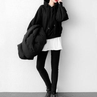 黒プルオーバーパーカー×黒スキニーパンツを着た女性
