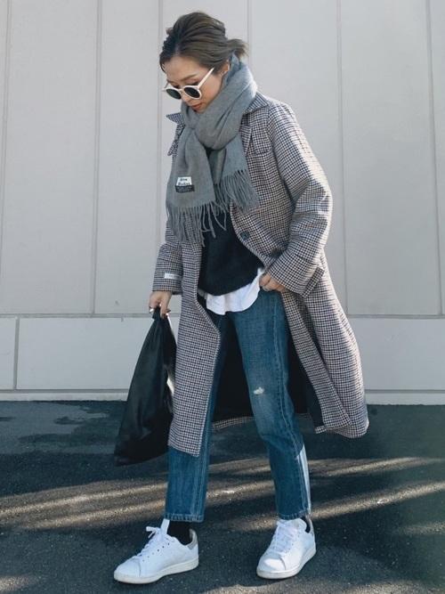 グレーのチェック柄コートとスリムジーンズを着た女性