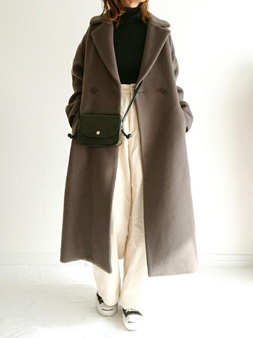 カーキステンカラー ロングコート×ブラックワイドリブタートルニットを着た女性