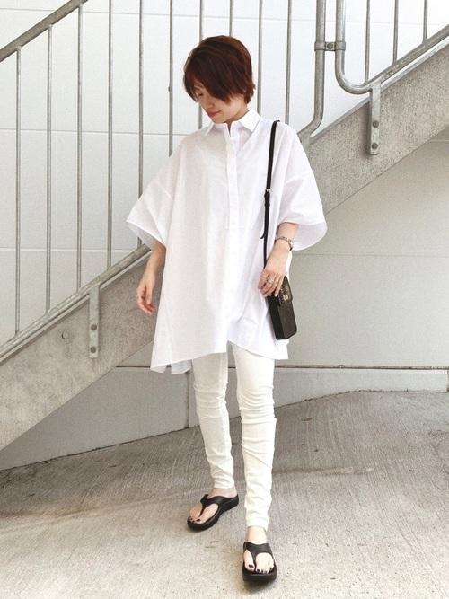 オーバーサイズシャツブラウス×白スキニーパンツを着た女性