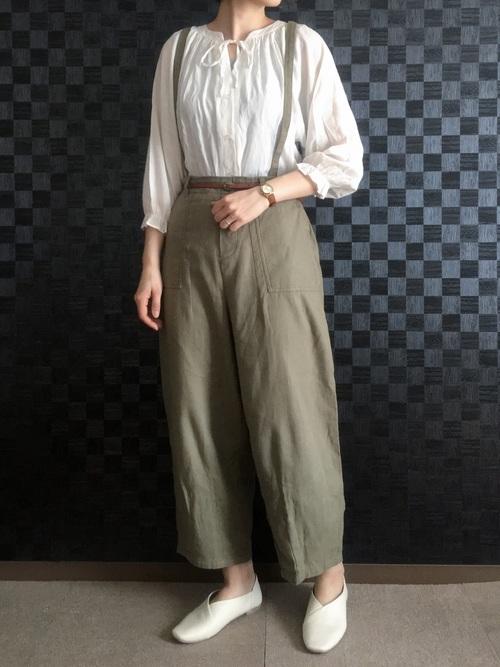 白ペザントブラウス×カーキサスペンダー付きパンツを着た女性