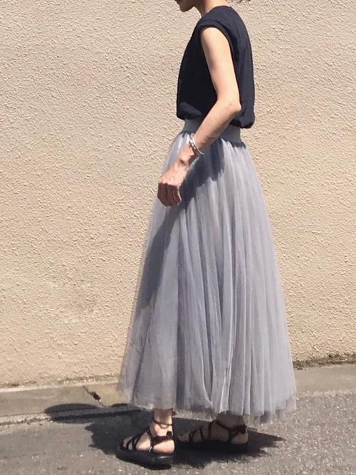 ノースリーブTシャツにグレーボリュームチュールロングスカートを履いた女性