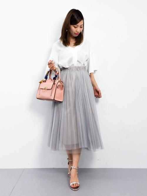 ボリュームフレアブラウスにグレーチュールスカートを履いた女性